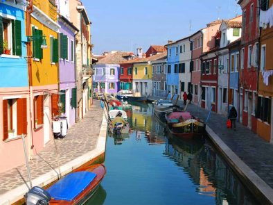 Colorful houses and boats lined up in the canal on a tour of Murano and Burano islands.