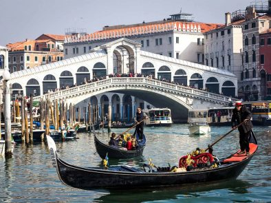 Guests enjoying a gondola tour in Venice while others walk over a white bridge.
