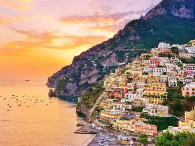 Colorful buildings built into the mountains overlooking the shore of the amalfi coast.