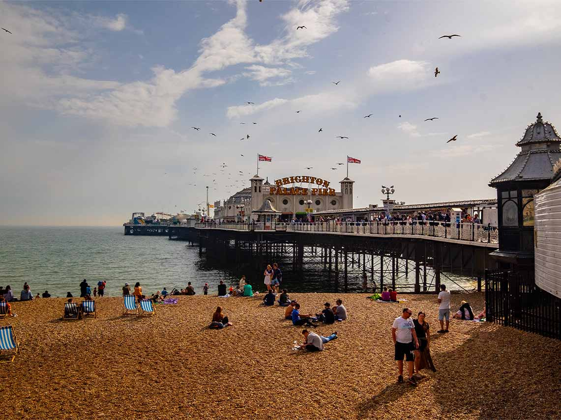 Guests on tour enjoying the beach at Brighton Pier.