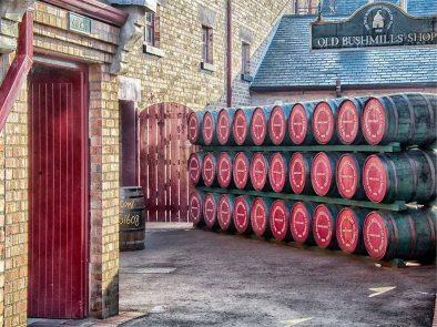whiskey casks stacked outside bushmills distillery in ireland.