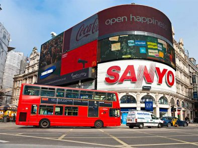 A red bus driving by Piccadilly Circus in London.