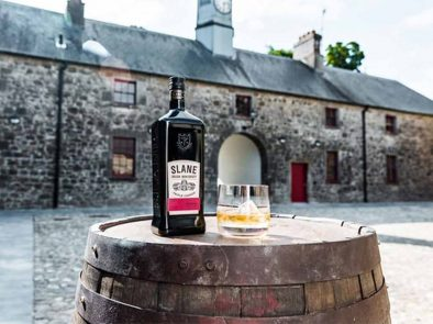 A bottle of slane whiskey sitting on top of a barrel for clients to enjoy after their distillery tour.